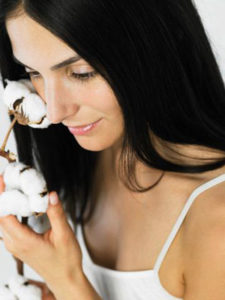 Woman Touching Cotton Plant to Face --- Image by © Whitemann/Corbis